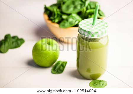 Juice jar with granny smith and basil on the table