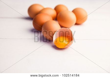 Brown eggs with one broken egg on the table