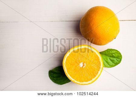 Overhead view of orange with basil leaves on the table
