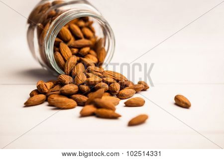 Almonds spilling from a jar on the table