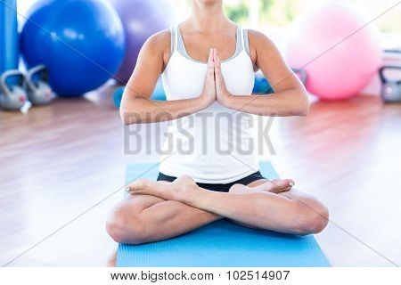 Low section of woman doing lotus posture with hands joined in fitness studio