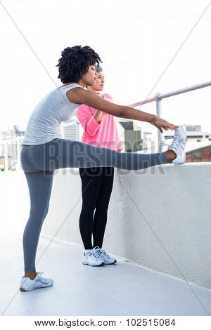Full length of fit women stretching by railing
