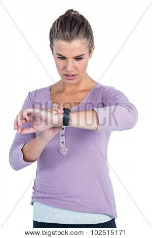 Young woman checking wristwatch against white background
