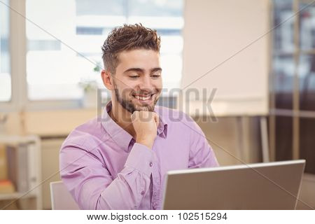 Happy handsome businessman with hand on chin looking at laptop in office