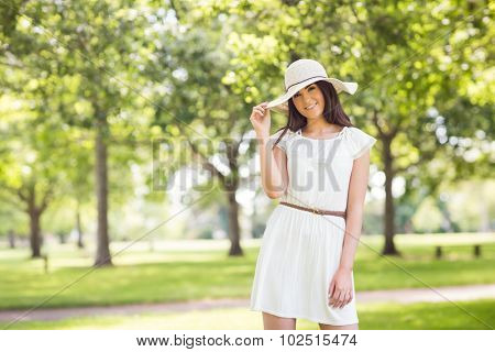 Portrait of confident smiling woman holding sun hat while standing on grassland