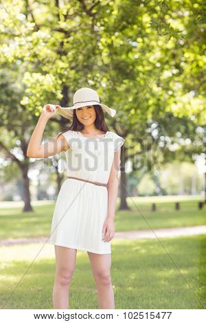 Portrait of confident happy woman holding sun hat while standing on grassland