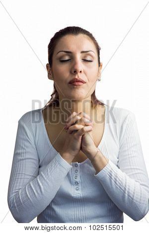 Beautiful woman praying with joining hands and eyes closed against white background