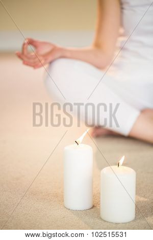 Low section of woman in yoga pose with illuminated candles on foreground