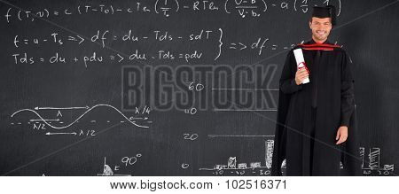 Charming graduate boy with his diploma against blackboard