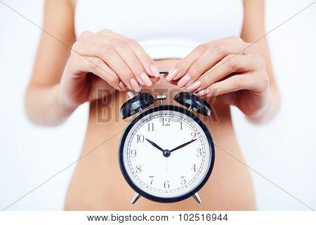 Fit female holding alarm clock