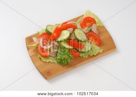 fresh vegetables with tuna chunks on wooden cutting board