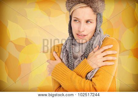 Attractive blonde wearing a warm hat against autumnal leaf pattern in warm tones