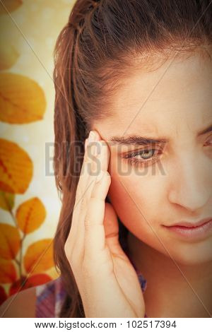 Close-up of beautiful woman suffering from headache against autumn scene