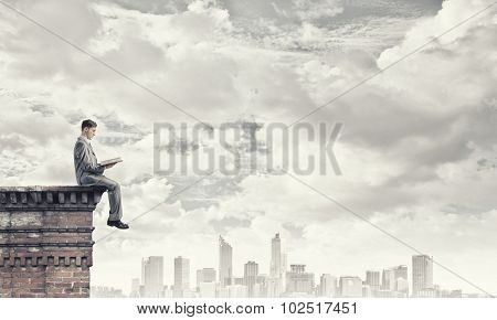 Young businessman sitting on building top and reading book