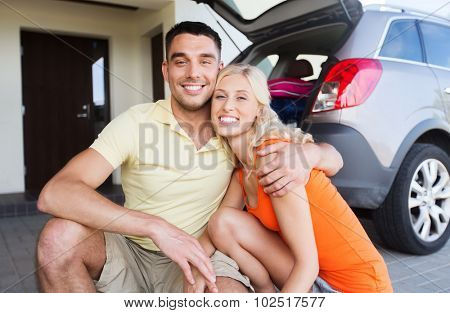 transport, leisure, family and people concept - happy couple hugging at home car parking space