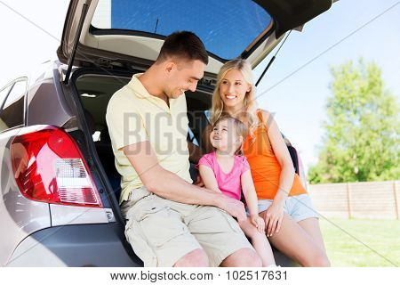 family , transport, leisure, road trip and people concept - happy man, woman and little girl sitting on trunk of hatchback car and talking outdoors