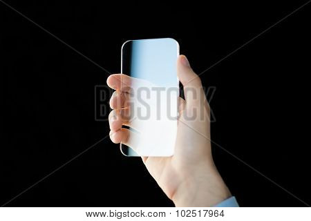 business, future technology and people concept - close up of male hand holding and showing transparent smartphone over black background