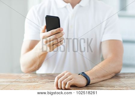 business, technology and people concept - close up of male hand holding smart phone and wearing heart-rate watch at home