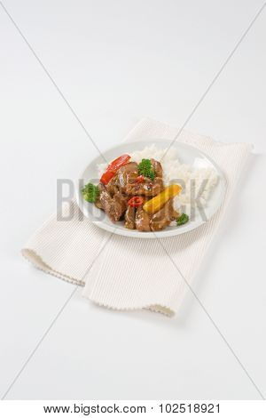 plate of rice, pan roasted meat and vegetables on white place mat