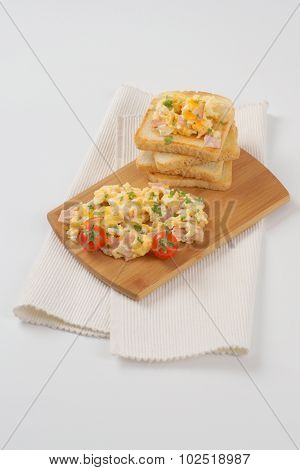 toasts and scrambled eggs on wooden cutting board and white place mat