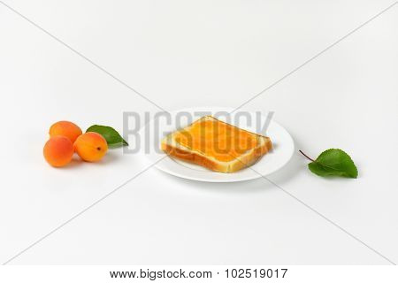 white toast with apricot marmalade served on the plate and accompanied by three fresh apricots