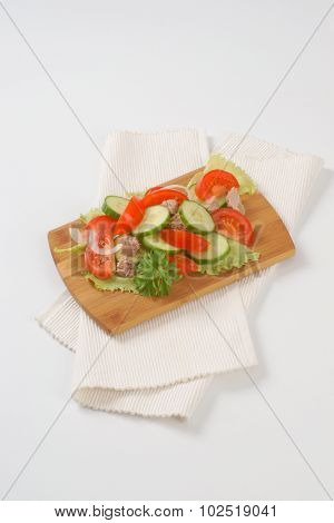 fresh vegetables with tuna chunks on wooden cutting board and white place mat