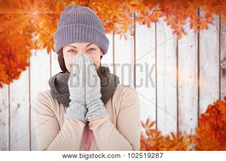 Smiling brunette wearing warm clothes against autumn leaves pattern