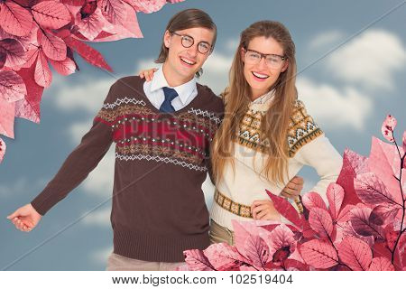 Happy geeky hipster couple embracing against cloudy sky