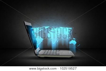 technology, mass media and global business concept - open laptop computer with world map over dark gray background
