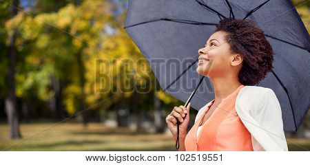 business, weather, season, fall and people concept - young smiling african american woman with umbrella over autumn park background