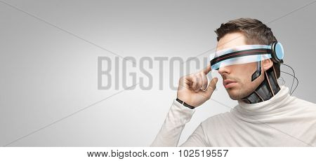 people, technology, future and progress - man with futuristic 3d glasses and microchip implant or sensors over gray background