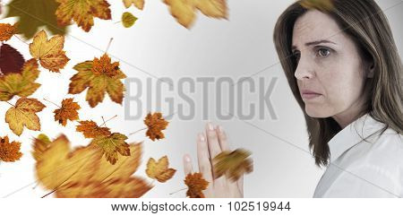 Depressed businesswoman looking away against autumn leaves