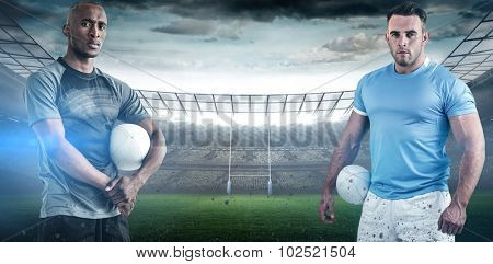 Portrait of confident sportsman with rugby ball against rugby stadium