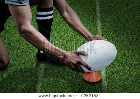 Cropped image of sportsman keeping rugby ball on kicking tee against pitch with lines