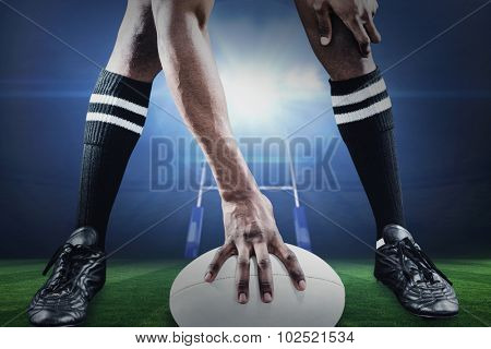 Low section of athlete playing rugby against rugby stadium