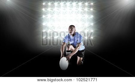 Rugby player holding ball while kneeling against spotlight