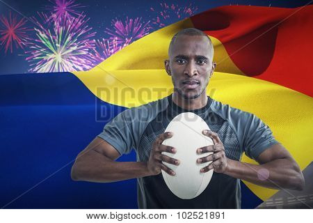 Portrait of athlete pressing rugby ball against fireworks exploding over football stadium