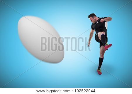 Rugby player kicking against blue background with vignette