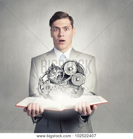 Businessman holding book and gears flying out of pages