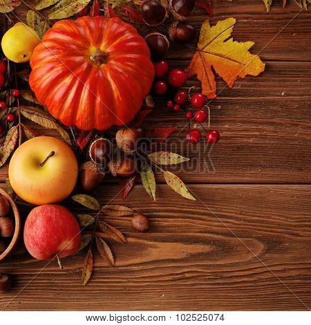 colorful leaves, pumpkin, apples and mushrooms on wooden background