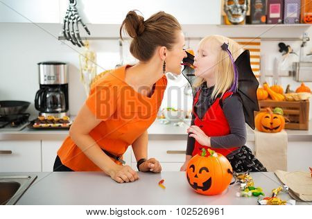 Funny Mother With Daughter In Bat Costume Eating Halloween Candy