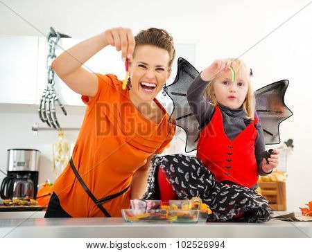 Halloween Dressed Girl With Mother Showing Gummy Worm Candies