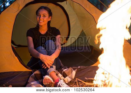 Portrait of a happy woman sitting near bonfire in the forest