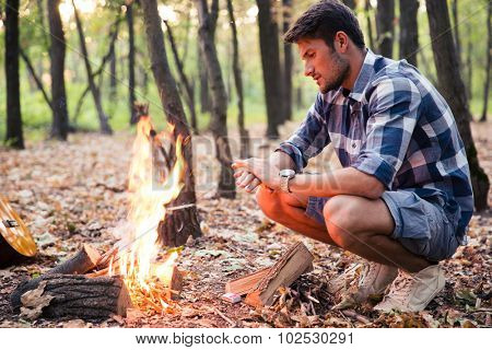 Portrait of a handsome man sitting near bonfire in the forest