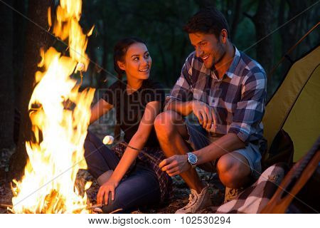 Couple fried sausages on bonfire in the forest