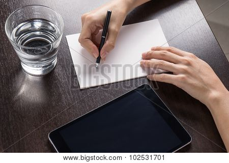 Close Up Of Woman With Tablet And Write A Paper On Wood Table