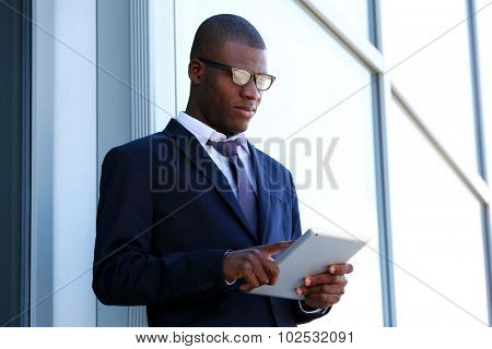 Handsome African American businessman with digital tablet near business centre