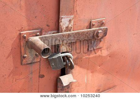 Detail Of Closed Rusty Door With Padlock