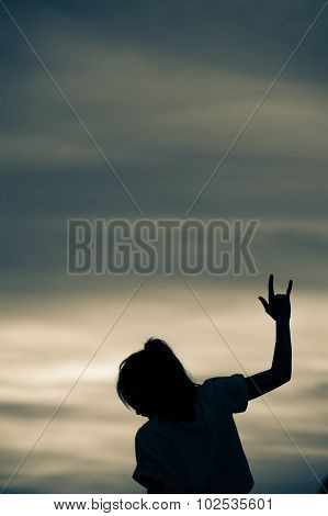 Silhouette of girl show hands love sign.