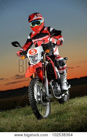 Man riding dirt bike at sunset over grassy area